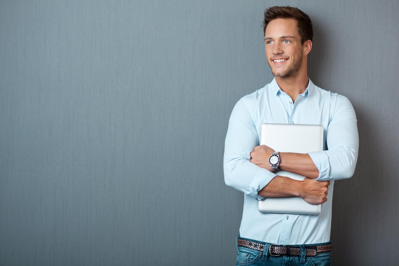 Student mit Laptop in der Hand steht vor Wand
